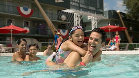 Family of 4 laugh while playing in the pool at Disney's All Star Sports Resort