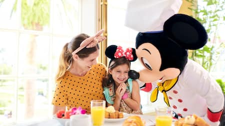 Mickey Mouse visits a woman and her daughter having breakfast
