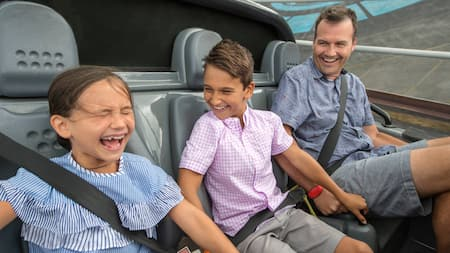 A dad and his 2 kids laugh while riding Test Track at Epcot