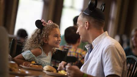 A little girl in Minnie Mouse ears and a her father smile while eating breakfast