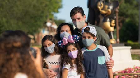 A family stands together wearing face coverings in front of partner's statue at Disney World while PhotoPass takes their photo