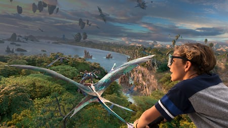 A boy flies through the sky with Na'vi and Mountain Banshees through the skies over Pandora
