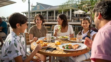 A family of 5 dining at an outdoor table at Disney Springs