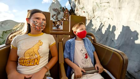 Dos preadolescentes con mascarillas pasean en Expedition Everest