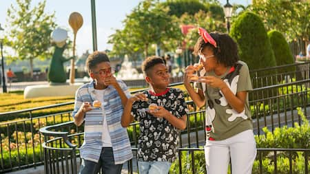 Trois préadolescents passent un bon moment ensemble en mangeant au World Showcase à Epcot