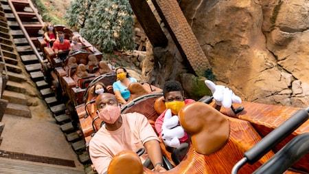 Several people riding on Seven Dwarfs Mine Train at Magic Kingdom park