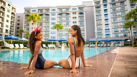2 Guests sit by the pool at Disney's Riviera Resort