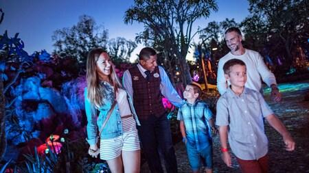 Uma família de 4pessoas caminhando com um Funcionário Disney por Pandora – The World of Avatar