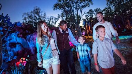 Una familia de 4personas con un Miembro del Elenco caminando por Pandora – The World of Avatar