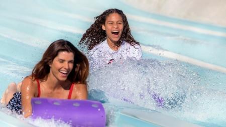 2 women slide down a waterslide on mats that resemble toboggans