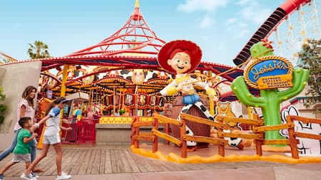 Una mamá y sus hijos se acercan a Jessie's Critter Carousel