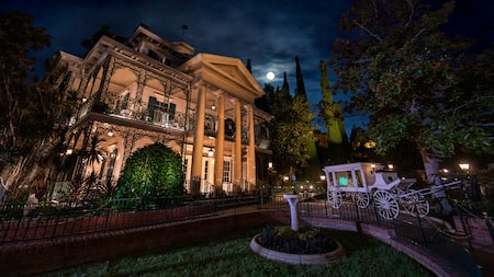 Under moonlit skies, a horse-drawn carriage sits outside the eerily illuminated exterior of the Haunted Mansion