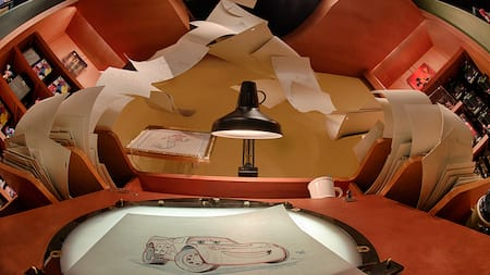Sketches of cars at Cars Land on and around a desk with a big desk lamp
