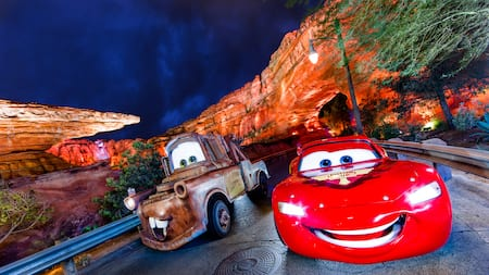 Lightning McQueen and Mater drive side by side on the track at Cars Land