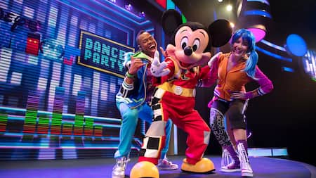 Mickey Mouse and 2 flashy costumed singing dancers smiling on the Dance Party stage
