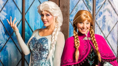 Anna and Elsa from Frozen pose in front of palace doors