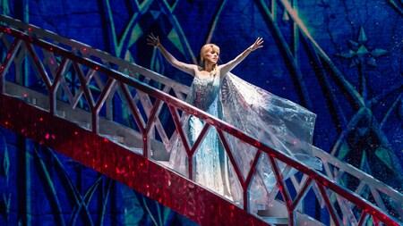 La princesa Elsa desciende por una ostentosa escalera, preparándose para crear hielo