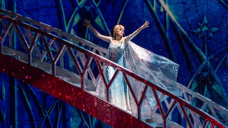 Princess Elsa descends a flashy staircase, preparing to create ice