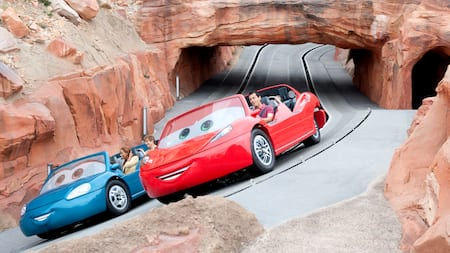 2 Radiator Springs Racers carry Guests past a tunnel in a rocky hill