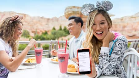 A teen Guest demonstrates a food order on a mobile device while her friends eat in the background