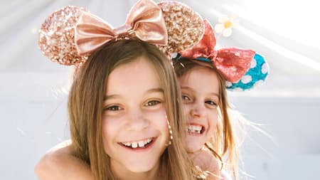 2 jóvenes Visitantes con Orejas de Mickey