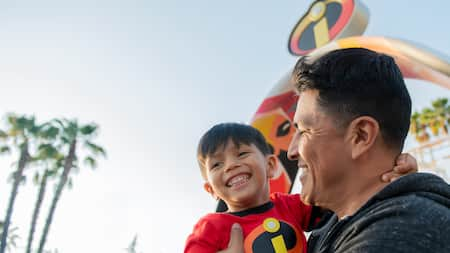 A father shares a joyful moment with his son in front of Incredicoaster