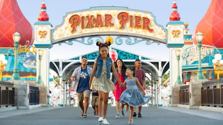 A young Guest in Minnie Ears leads her happy family through Pixar Pier