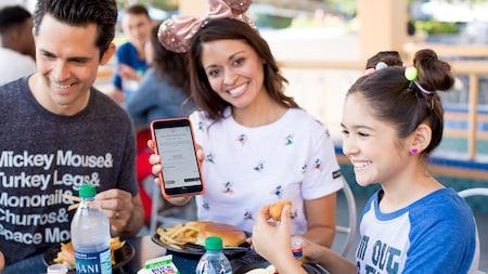 Una mamá muestra un pedido móvil en un dispositivo electrónico mientras su familia come