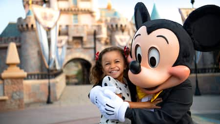 Mickey Mouse hugs a young Guest in front of the castle