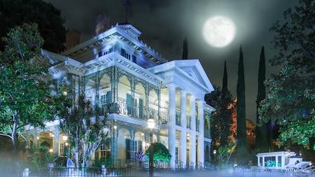 Una luna llena ilumina la atracción Haunted Mansion de noche