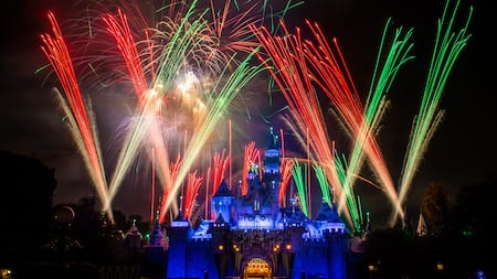 A fireworks display surrounds Sleeping Beauty Castle at night