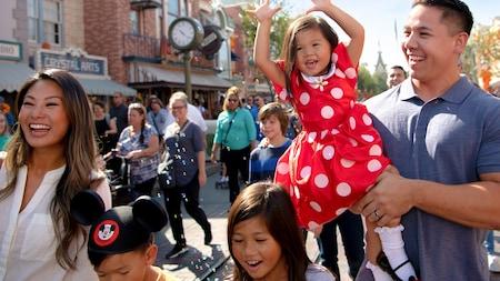 Una niña pequeña con un vestido de Minnie Mouse va en brazos de su padre mientras su familia camina por Main Street U.S.A.