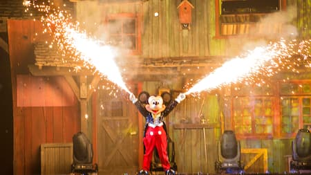 On a performance stage, Mickey Mouse shoots fire out of his fingertips