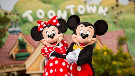 Mickey and Minnie Mouse posing in front of a sign reading Toon Town