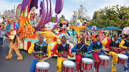 High stepping drummers front a parade that includes Mickey Mouse and Pluto