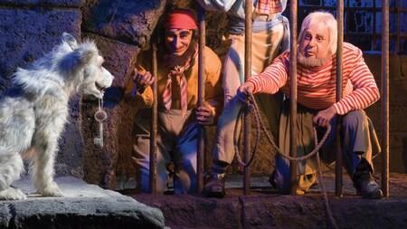 Delincuentes encarcelados intentan atraer a un perro que sostiene una llave en la atracción Pirates of the Caribbean