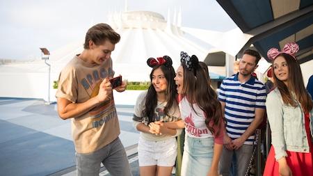 Visitantes adolescentes en la fila de una atracción se entusiasman sobre las opciones de la Aplicación Disney Play en un teléfono celular