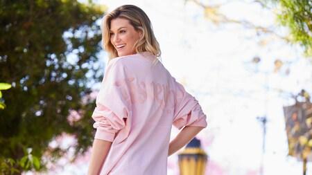 Un Visitante, sonriendo en una camisa rosa