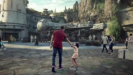 A parent and child excitedly approach a star ship at Star Wars Galaxys Edge
