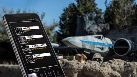 A galactic handheld mobile device displays symbols and characters in Aurebesh, a language used in Star Wars, as a starship looms nearby on the landing pad