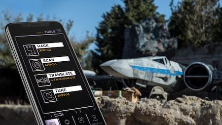 Un dispositivo móvil intergaláctico muestra símbolos y caracteres en Aurebesh, un idioma utilizado en Star Wars, mientras una nave espacial se aproxima a la zona de aterrizaje
