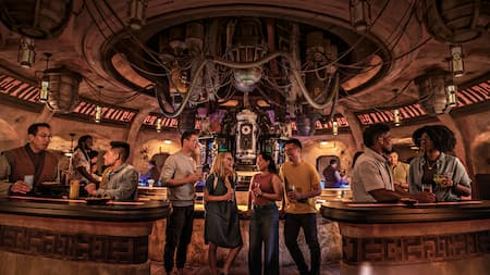 Adults enjoy exotic beverages inside a Star Wars cantina with hoses, tubes and unusual machines