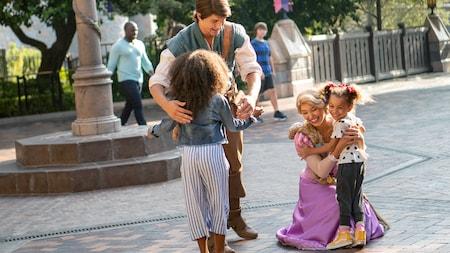 Dos actores vestidos como Rapunzel y Flynn Rider abrazan a dos niñas pequeñas mientras otros Visitantes pasan por allí en el fondo