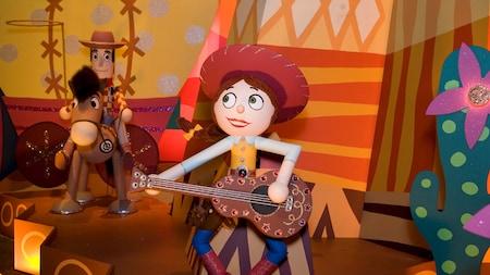 Jessie toca la guitarra y Woody cabalga en su corcel en it's a small world
