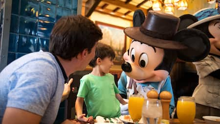 At Storytellers Cafe, Mickey Mouse is dressed as an explorer and greets a father and son.