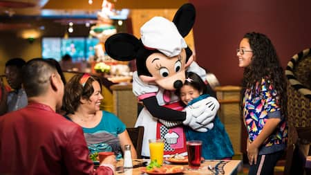 A happy family watches as Minnie Mouse, dressed as a chef, hugs one of their children