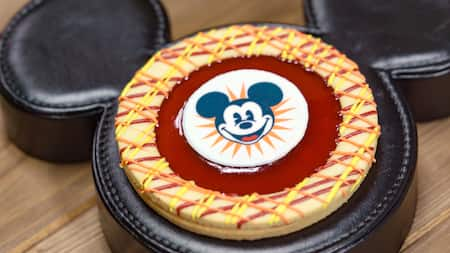 A Mickey Mouse themed cookie seated on a large pad in the iconic shape of his head