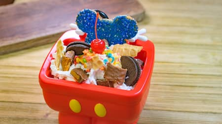 A Mickey Mouse themed bowl filled with cookie crumbles, sprinkles, ice cream and waffle cone crumbles