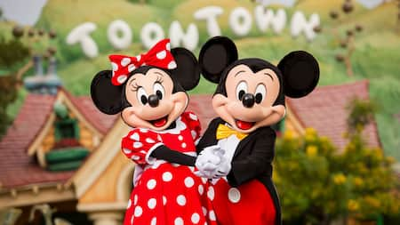 Minnie Mouse and Mickey Mouse pose together, holding hands in front of Mickey's Toontown