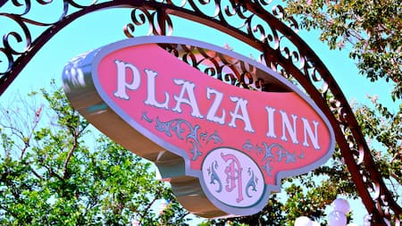 An ornate hanging sign identifies the entrance to Plaza Inn